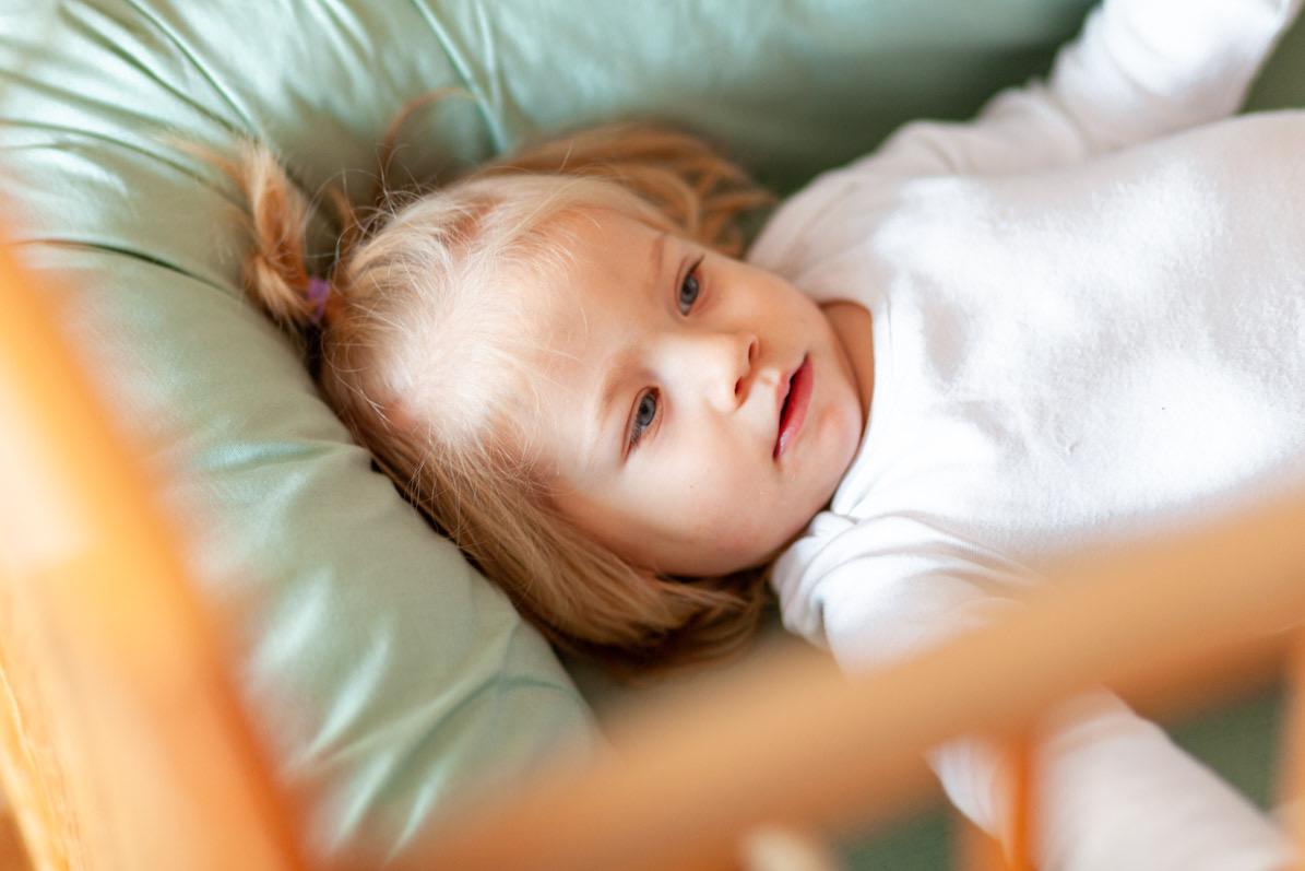 Fotografie dítěte v postýlce při rodinném focení